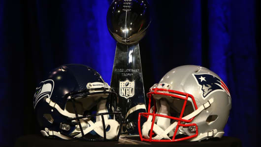 The Vince Lombardi Trophy is displayed between the helmets of the Seattle Seahawks (L) and New England Patriots.