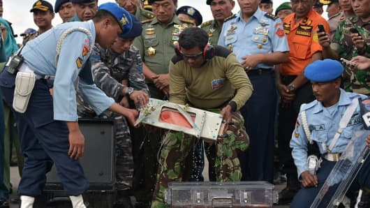 Indonesian officers move the flight data recorder of the AirAsia flight QZ8501