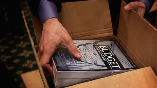 A committee staff brings out copies of the President's FY2016 budget from the boxes in the Senate Budget Committee room February 2, 2015 on Capitol Hill in Washington, DC.