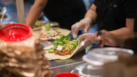Employees prepare lunch orders at a Chipotle Mexican Grill restaurant at Madison Square Park in New York.