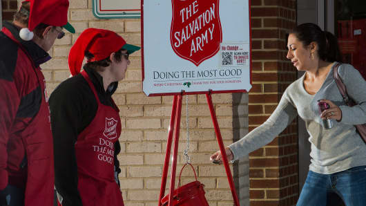 A woman(R) makes a donation into a Salvation Army kettle outside a Giant grocery store in Clifton, Virgina.