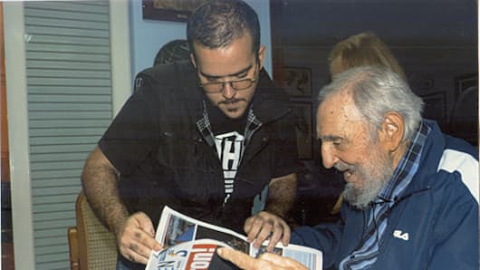 Former Cuban President Fidel Castro and President of Cuba's University Students Federation (FEU) Randy Perdomo look at a newspaper during a meeting in Havana in this picture provided by Cubadebate.  The pictures of Castro with Perdomo were taken on January 23, 2015 according to Perdomo's account.