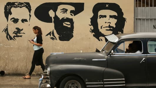 A young woman talks on her mobile phone as she walks past a mural depicting Cuban revolutionary leaders January 24, 2015 in Havana, Cuba.