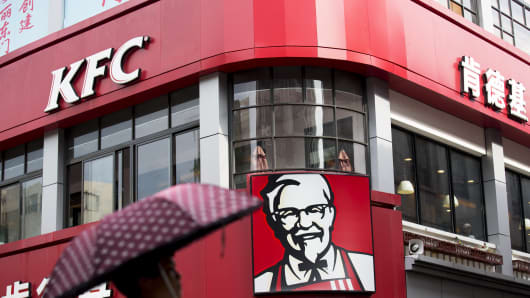 A woman holding an umbrella walks past a KFC restaurant, operated by Yum! Brands Inc., in the pedestrianized Dongmen area of Shenzhen, China.