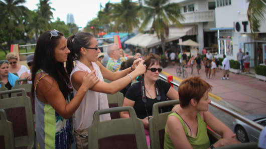 Tourists on the Big Bus Tour double decker bus during a sight-seeing trip to South Beach, Miami.