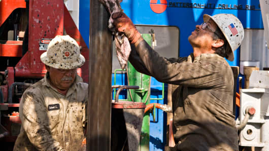 Rig floorhands clean a drilling pipe at a natural gas well in the Eagle Ford shale in Karnes County, Texas.