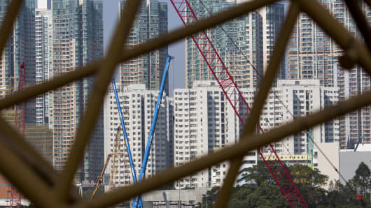 Residential buildings seen through a construction crane stand in the West Kowloon district of Hong Kong