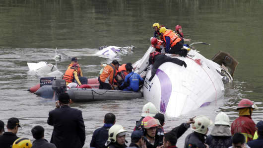 Rescuers pull a passenger out of the TransAsia Airways plane which crash landed in a river, in New Taipei City