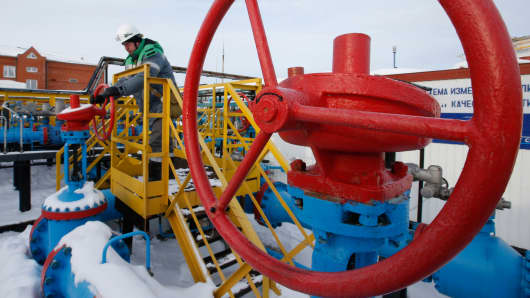 A worker adjusts the valve of an oil pipe at an oil reception and delivery point owned by Bashneft, near Ufa, in Russia's Republic of Bashkortostan.
