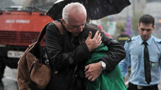 A 35-year-old woman is comforted after she was rescued at Athens' central Omonia square. She had climbed onto a metal sculpture and reportedly threatened to jump due to her economic situation.