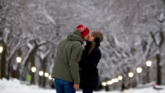 A couple kiss under snow and ice laden trees at The Mall in Central Park during a winter storm, New York, February 2, 2015.
