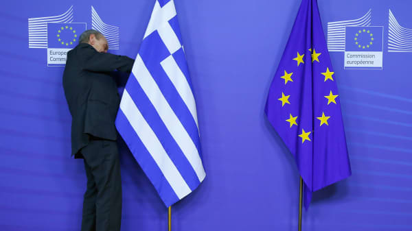 A man adjusts a Greek flag ahead of the visit of Greek Prime Minister Alexis Tsipras at the European Commission headquarters in Brussels February 4, 2015.