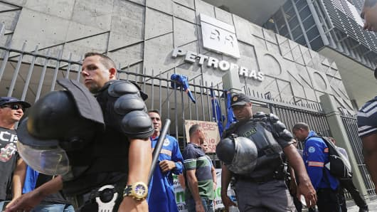 Workers gather at a protest in front of Petrobras headquarters, as military police walk by, Feb. 4, 2015, in Rio de Janeiro.