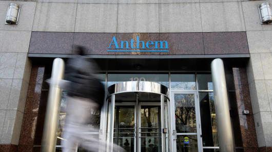A pedestrian walks past the corporate headquarters of health insurer Anthem, in Indianapolis.