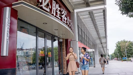 Pedestrians walk past a Pizza Hut restaurant in Beijing.