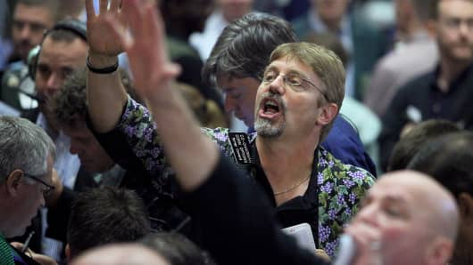 Traders work in trading floor of the CME Group's Chicago Board of Trade in Chicago.
