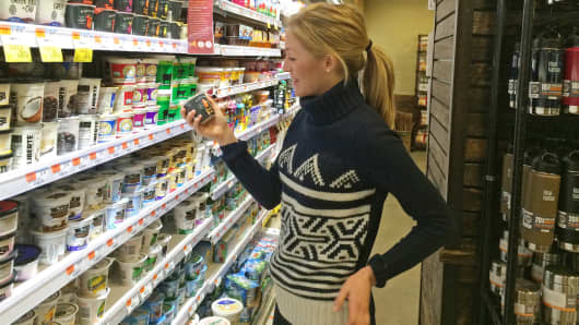 Elly Truesdell inspecting product at a Whole Foods store