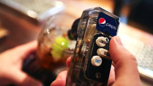 An employee pours Pepsi from a soft drink pump behind the bar of a restaurant.