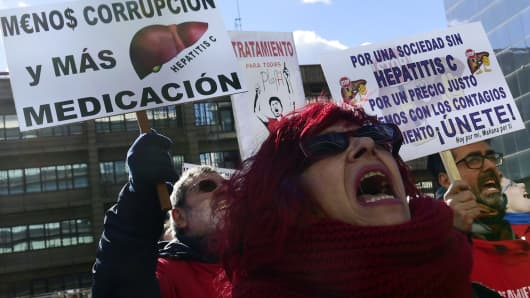 Hepatitis C sufferers and supporters hold placards during a demonstration outside of US laboratory Gilead Sciences office in Madrid on February 5, 2015.