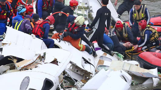 Rescue teams work to free passengers from the TransAsia Airways ATR 72-600 turboprop airplane that crashed into the Keelung River, Taipei.