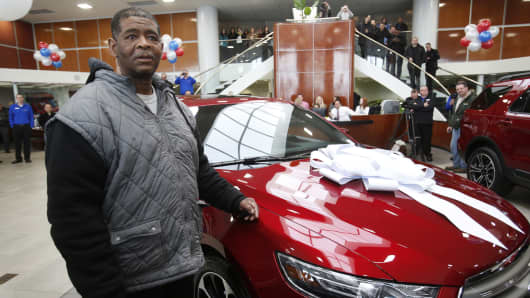 Detroit resident James Robertson reacts next to the 2015 red Ford Taurus sedan he was surprised with as a free gift at the Suburban Ford dealership in Sterling Heights, Mich., February 6, 2015.