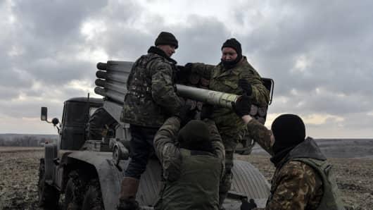 Ukrainian servicemen load rockets before launching them toward pro-Russian separatist forces outside Debaltseve, eastern Ukraine February 8, 2015.