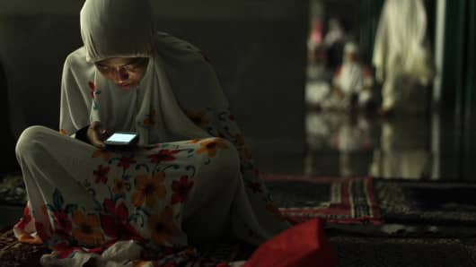 A Muslim woman uses her phone before the start of an evening mass prayer session in Indonesia.