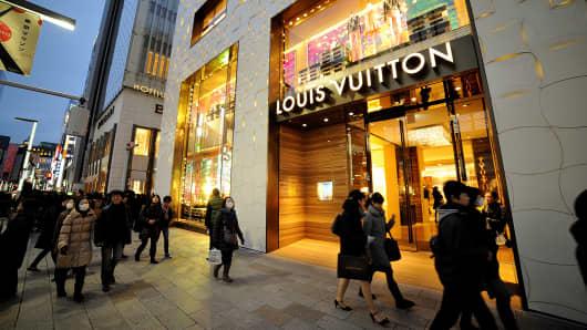 People walking past Louis Vuitton store