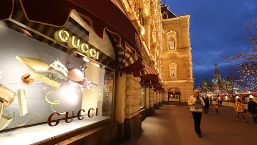 Pedestrians pass a display of Gucci products in a department store in Moscow.
