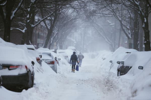 Pedestrians make their way along a snow covered street during a winter snow storm in Cambridge, Massachusetts February 9, 2015.
