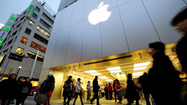 Shoppers walk by an Apple store in Tokyo, Feb. 07, 2015.