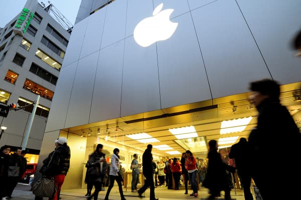Shoppers walk by an Apple store in Tokyo, Feb. 07, 2015.