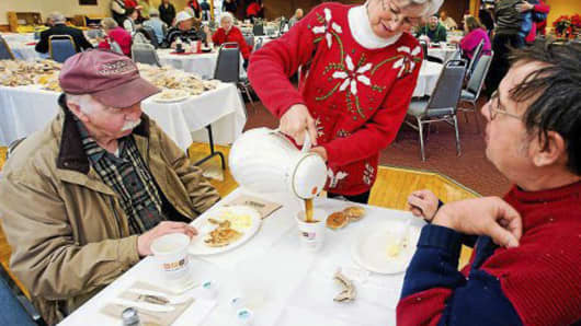 In this December 2011 photo, Connie Howe pours coffee for Ronald Read, left, and Dave Smith during the Charlie Slate Memorial Christmas breakfast at the American Legion in Brattleboro, Vt.