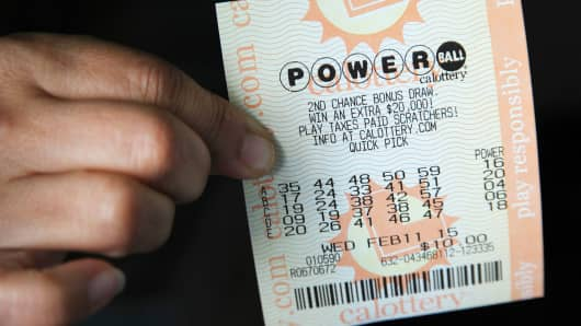 A woman holds a ticket purchased for Wednesday's estimated Powerball lottery jackpot of $450 million in Los Angeles, February 11, 2015.