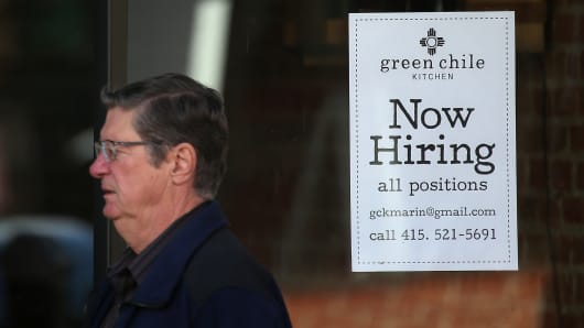 A pedestrian walk by a now hiring sign posted in the window of a business in San Rafael, Calif.