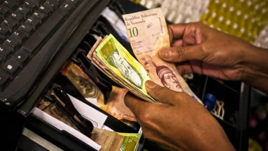 An employee at a restaurant counts bolivar notes in a photograph taken in Caracas, Venezuela.