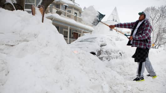 A file photo showing a local resident digging out his car from snow in the Dorchester neighborhood of Boston.