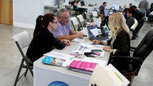 People sit with an insurance advisor as they sign up for Obamacare in Miami.