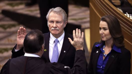 In this Jan. 12, 2015 file photo, Oregon Gov. John Kitzhaber, is joined by his fiancee, Cylvia Hayes, as he is sworn in for a fourth term by Senior Judge Paul J. De Muniz in Salem, Ore.