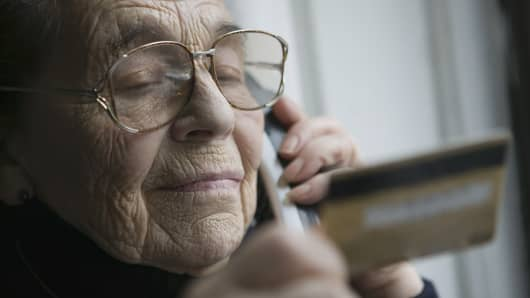Senior woman on telephone holding credit card