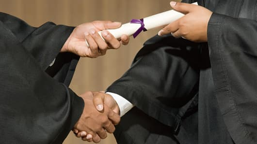 Student getting diploma and handshake
