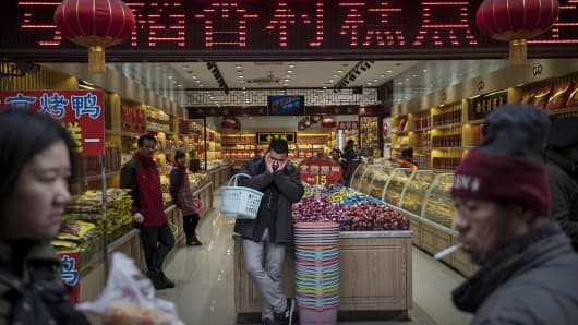 A Chinese customer rests as he stands in a store in a shopping district on January 20, 2015 in central Beijing, China.