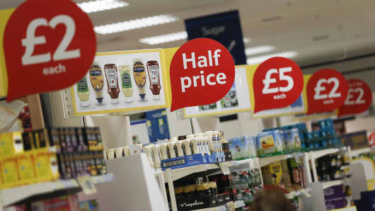 Discount and half-price signs sit above goods displayed for sale on the end of aisles inside a Tesco Extra Supermarket