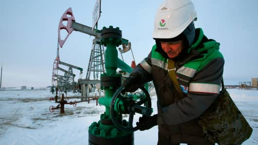 A worker checks the valve of an oil pipe at an oil field near the village of Nikolo-Berezovka, Russia.