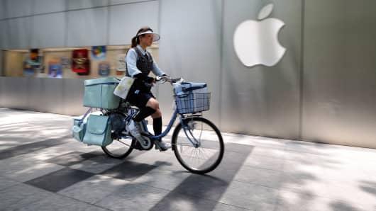Woman biking past Apple store