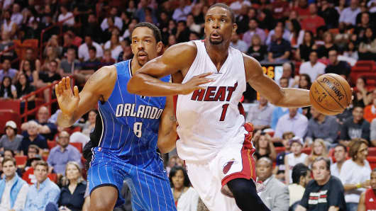 Miami Heat's Chris Bosh (1) drives past Orlando Magic's Channing Frye (8) in Miami, Dec. 29, 2014.
