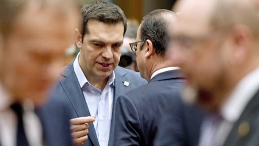 Greek Prime Minister Alexis Tsipras, left, speaks with French President Francois Hollande before a meeting as part of the European Council Summit at the European Union Headquarters in Brussels, Feb. 12, 2015.