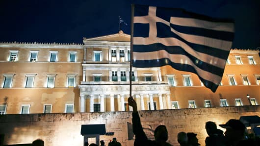 A protester waves a Greek national flag during an anti-austerity pro-government demonstration in front of the parliament in Athens February 16, 2015.