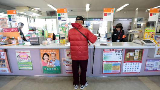 Customer Katsumi Amano withdraws money from his bank account at a Japan Post Co. branch in Hachioji, Japan, on Tuesday, April 15, 2014.