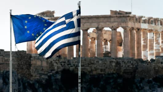 A European Union and a Greek national flag flutter in front of the Parthenon temple in Athens February 11, 2015.